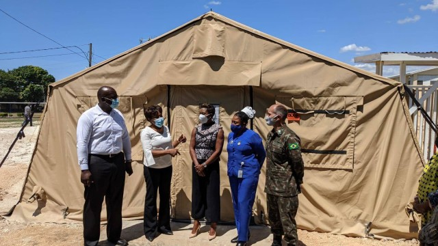 Brig. Gen. Alcides V. Faria, right, U.S. Army South deputy commanding general for interoperability, receives a tour by representatives of the Ministry of Health and Wellness of a U.S.-funded mobile field hospital based at the Spanish Town Hospital in St. Catherine, Jamaica, April 29, 2021.