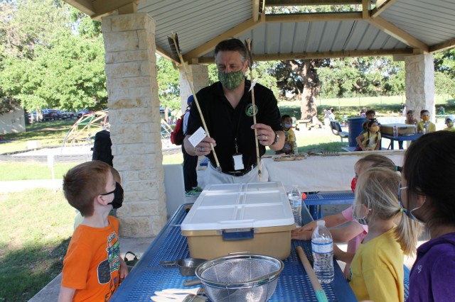 Chris Leach, a conservation biologist, shows arrows at the Archaeology station during the U.S. Army Environmental Command Nature Walk held for about 140 kindergarteners from the Fort Sam Houston Elementary School.