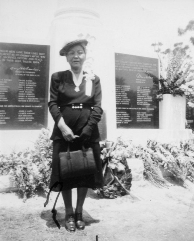 Nawa Munemori stands in front of a monument honoring her son, Army Pfc. Sadao Munemori, at Evergreen Cemetery in Los Angeles. She wears the Medal of Honor she received on his behalf.