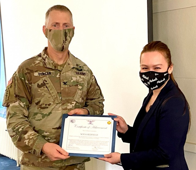 Sophia Redfield, right, receives the ICE Customer Service award from Col. Skye Duncan, JBLM Garrison commander, May 4, at Joint Base Lewis-McChord.