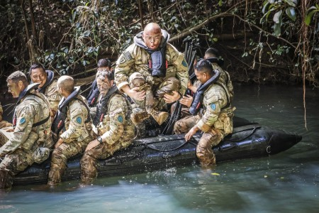 A soldier jumps out of a boat during competitive tactical events at Schofield Barracks, Hawaii, April 8, 2021. The three-day series of events were designed to build cohesive teams.