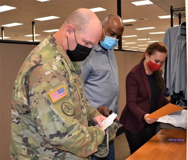 Joint Base Lewis-McChord employees Sophia Redfield, right, and Sterling Richardson, middle, assist Sgt. 1st Class Robert Pierce with passport paperwork at the Visa and Passport Office April 30 in Waller Hall.