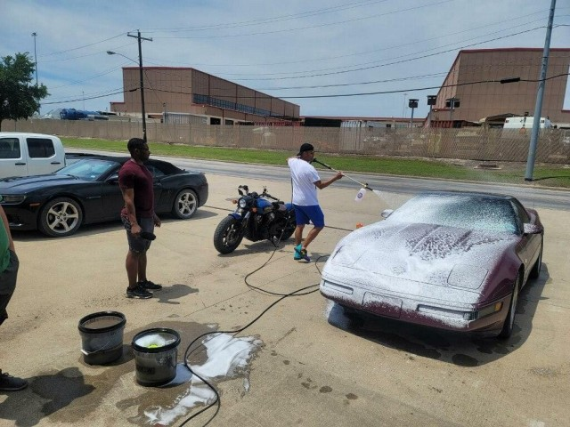 Soldiers Spray down and clean a vintage vehicle at Fort Hood during an FRG fundraising car wash.