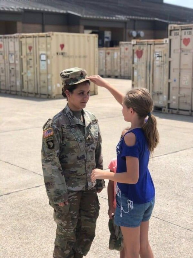 Staff Sgt. Christina Kring, recruiter, Catalina Recruiting Station, Tucson Recruiting Company, has the rank of staff sergeant pinned on her uniform by her stepdaughter Jailynn during a promotion ceremony, Aug. 1, 2019, Fort Campbell, Kentucky. (Courtesy Photo)