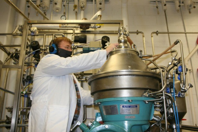 Joe Kragl, a Center biologist, operates a centrifuge in the extraction phase; it contains a bucket that functions like a large salad spinner, separating the microbes from the broth.