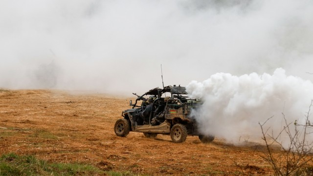 Members of the opposing forces team from 1st Battalion, 4th Infantry Regiment deploy smoke from the back of their all-terrain vehicle during the Dragoon Ready 21 training exercise at Hohenfels Training Area, Germany, April 19, 2021. Dragoon Ready 21 is a 7th Army Training Command-led exercise conducted in HTA, Germany. (U.S. Army photo by Master Sgt. Ryan C. Matson)