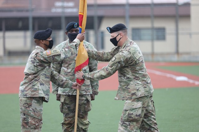 Brig. Gen. Steven Allen, commander, 19th Expeditionary Sustainment Command, passes the command colors to Sgt. Maj. Larry Cuffie, NCOIC of ceremony, during a relinquishment of responsibility ceremony for Command Sgt. Maj. LaDerek Green, center, on Camp Walker, Republic of Korea.