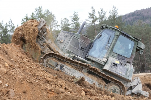 A U.S. Army Soldier assigned to the 2nd Cavalry Regiment digs dirt using an armored bulldozer during Dragoon Ready 21 at the Hohenfels Training Area, April 17, 2021. Daily training, conducted in realistic environments, under realistic circumstances, ensures our forces maintain the highest levels of proficiency and readiness for worldwide deployment. (U.S. Army photo by Sgt. Julian Padua)