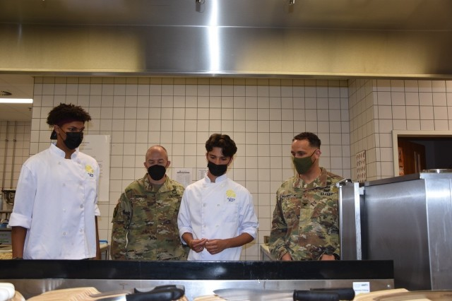 Dom Bivins, left, and Alex Arcila explain to Brig. Gen. Jed Schaertl and Col. Mario Washington some of the techniques they used to prepare their award winning meal from the Europe East Culinary Competition.