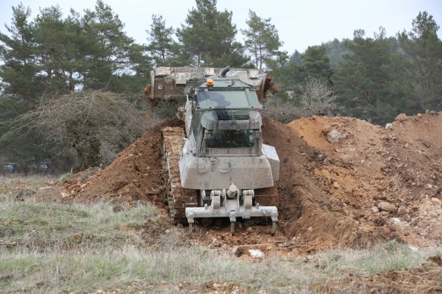 An armored bulldozer assigned to the 2nd Cavalry Regiment drags dirt during Dragoon Ready 21 at the Hohenfels Training Area, April 17, 2021. Daily training, conducted in realistic environments, under realistic circumstances, ensures our forces maintain the highest levels of proficiency and readiness for worldwide deployment. (U.S. Army photo by Sgt. Julian Padua)
