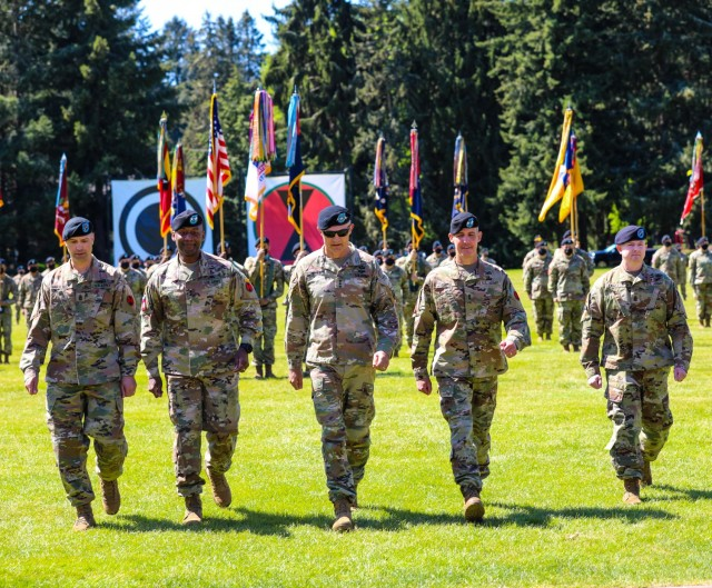The incoming and outgoing 7th Infantry Division command teams led by America's First Corps commander Lt. Gen. Randy George at the change of command and responsibility ceremony at JBLM, May 11, 2021. (From Left to Right) Outgoing command team: Command Sgt. Maj. Robin M. Bolmer and Maj. Gen. Xavier T. Brunson, First Corps commander Lt. Gen. Randy George, and incoming commander Maj. Gen. Stephen Smith and Command Sgt. Maj. Timothy Lawless.  (US Army Photo by Spc. Christopher Wilkins, 7th Infantry Division)