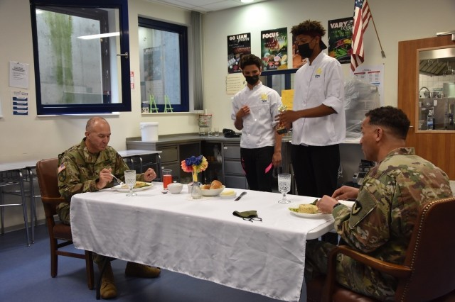 Brig. Gen. Jed Schaertl, left and Col. Mario Washington enjoy the Europe East Culinary Competition winning menu of Creamy Tuscan Chicken, Rice Pilaf and Lemon Grilled Asparagus as Dom Bivins and Alex Arcila talk to the commanders about winning the culinary arts competition.