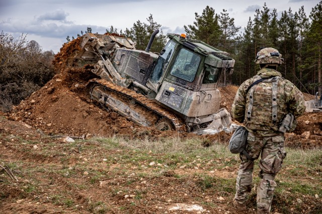 U.S. Army Pvt. Dalton Leonard, a D6K Light Bulldozer operator assigned to Beast Troop, Regimental Engineer Squadron, 2nd Cavalry Regiment, moves earth to create a berm and ditch to deter enemy movement in the area as part of exercise Dragoon Ready 21 at Hohenfels Training Area, Germany, April 17, 2021. Sgt. 1st Class Cody Williams, a platoon sergeant, also assigned to Beast Troop, ensures the earth modification standards are met. Dragoon Ready 21 is a 7th Army Training Command-led exercise, which provides the 2nd Cav. Regt. with the opportunity to en-hance readiness and train on its core tasks. (U.S. Army photo by Staff Sgt. Christopher Stewart)