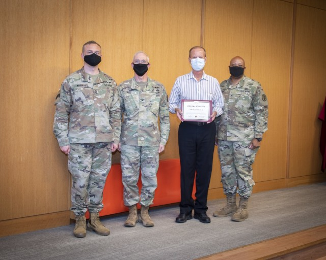 Brig. Gen. Shan K. Bagby, U.S. Army Regional Health Command – Central commanding general, Col. Michael Wirt, Brooke Army Medical Center commander, and Sgt. Major Gabriel Wright, chief clinical noncommissioned officer, present Michael Dulevitz, chief of Volunteer Services, with a Lifetime of Service award at a ceremony in the Carolyn D. Putnam Auditorium, Fort Sam Houston, Texas, May 11, 2021. The ceremony was held to honor BAMC's 18 civilian employees who have been in federal civil service for 45 years or more. (U.S. Army photo by Jason W. Edwards)