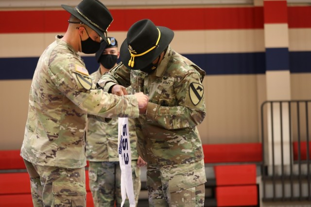 Capt. Austin Harper and 1st Sergeant Jonathan Collier remove the old 289th Supply Company guidon and install the new A Company guidon during the 553rd Division Sustainment Support Battalion conversion ceremony April 16 at Fort Hood.