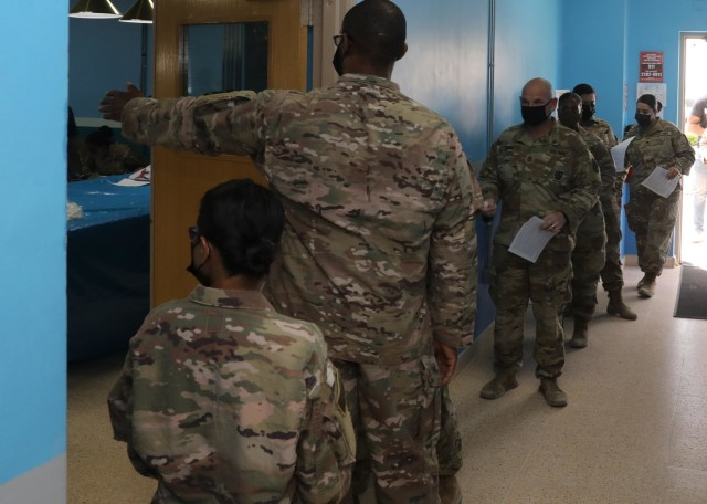 """Soldiers deployed to Camp Arifjan, Kuwait, line up May 5, 2021 to receive the COVID-19 vaccine upon the restart of vaccine administration after a month-long halt on vaccinations in the U.S. Central Command area of responsibility. The """"Desert Medics"""" of the Forest Park, Georgia, based 3rd Medical Command (Deployment Support) oversaw this vaccination station and coordinate CentCom's COVID-19 response program. (U.S. Army photo by Staff Sgt. Neil W. McCabe)"""