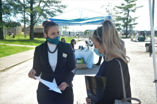 Migdalia Rosado Diaz, left, human resources specialist, Civilian Personnel Advisory Center, speaks with Sapphire Thal, Army spouse, May 6 during the Open Air Hiring Fair at the Spouse Employment Center. More than 100 people interacted with 23 employers and eight support organizations during the event.
