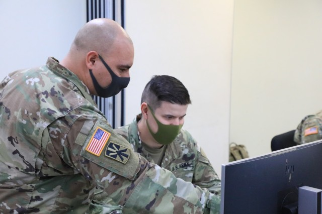Sgt. 1st Class Gregorio Estrada, Patriot Master Gunner course lead instructor from 3rd Battalion, 6th Air Defense Artillery Regiment located at Fort Sill, Oklahoma, guides Staff Sgt. Shane Viernum, Patriot fire control enhanced operator with 94th Army Air and Missile Defense Command, through a class assignment during the PMG couse at Kadena Air Base, Japan April 29. The Patriot Master Gunner Course is currently being held in Japan for the first time. Air Defenders across the Indo-Pacific region are gaining an advanced understanding of air defense operations, standards, and doctrine during PMG class 701-21 hosted by the 1st Battalion, 1st Air Defense Artillery Regiment at Kadena Air Base from April 19 to June 28, 2021.