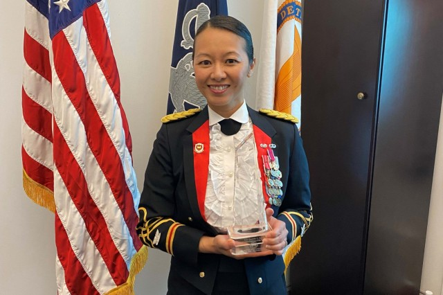 Army Col. Danielle Ngo, the executive officer to the Army Inspector General, displays her Asian-American Engineer of the Year trophy in her office at the Pentagon, May 4, 2021.