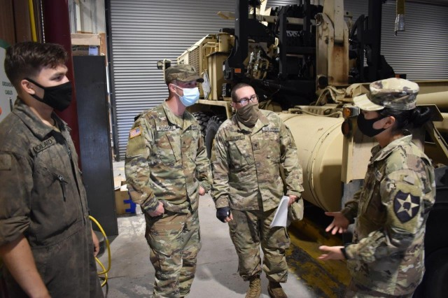 U.S. Army 2nd Lt. Pauline Heng (right), previously a mechanic in 1-2 Stryker Brigade, visits with her fellow mechanics in the 1-14 Cav. motor pool after returning as a commissioned officer following Officer Candidate School.