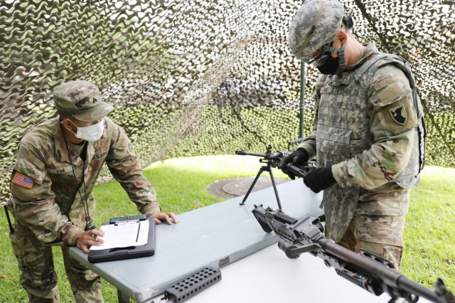 Sgt. Andrew Han, assigned to the 38th Air Defense Artillery Brigade, assembles an M9 handgun during the 2021 U.S. Army Japan Best Warrior Competition at Camp Zama, Japan, May 11. Sgt. Miguel Yap grades his performance.