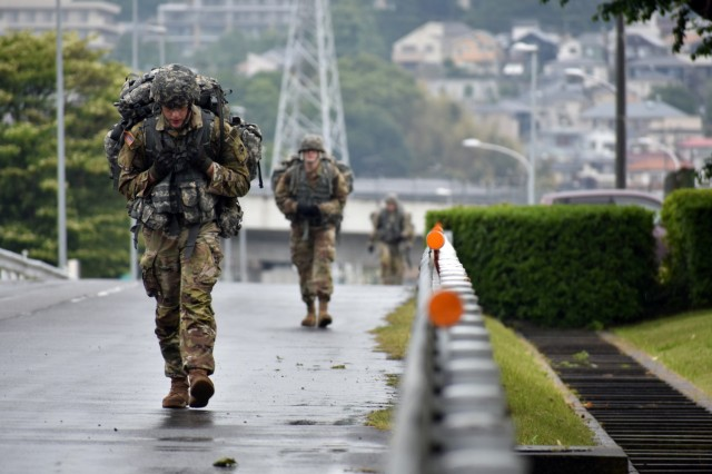 Spc. Kyle Hunsaker, front, assigned to the 247th Military Police Detachment, competes in the 12-mile ruck march during the 2021 U.S. Army Japan Best Warrior Competition at Sagami General Depot, Japan, May 13. Hunsaker came in second in the competition's Soldier category.