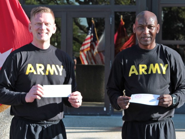 Maj. Gen. Darren Werner (left), Commanding General U.S. Army Tank-automotive and Armaments Command, and Command Sgt. Maj. Jerry Charles (right), TACOM, display their signed donation forms for the Army Emergency Relief campaign during a run/walk event at the Detroit Arsenal, Michigan May 14.