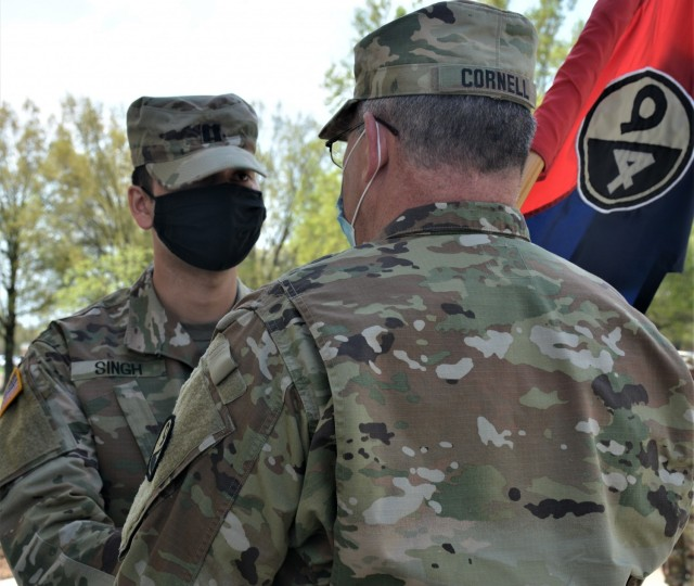 Capt. Alex Singh, outgoing commander (left), passes the unit guidon to Col. Cliffton Cornell, 94th Training Division-Force Sustainment Chief of Staff (right). Singh relinquished his command during the 94th TD-FS Headquarters and Headquarters Company change of command ceremony. The ceremony was held at Fort Lee's Combined Arms Support Command Headquarters to bid farewell to Singh and welcome Capt. Theang Sterns as the 94th TD-FS HHC commander on April 9, 2021. (Photo by Maj. Ebony Gay, 94th TD-FS Public Affairs Office)