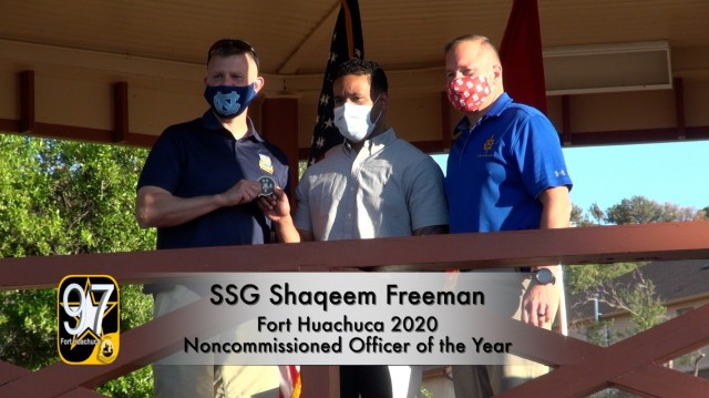 In this video capture, Command Sergeant Major Warren Robinson, Command  Sergeant Major of the U.S. Army Intelligence Center of Excellence presents a challenge coin to Staff Sgt. Shaqueem Freeman, the Fort Huachuca 2020 Noncommissed Officer of the year as  Maj. Gen. Anthony Hale, Commanding General, U.S. Army Intelligence Center of Excellence & Fort Huachuca looks on.