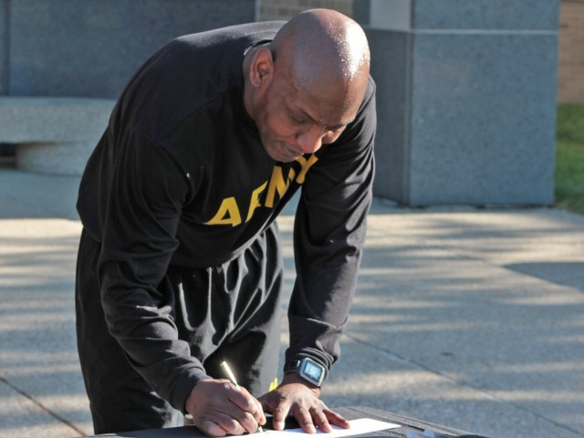Command Sgt. Maj. Jerry Charles, U.S. Army Tank-automotive and Armaments Command, signs his Army Emergency Relief donation during a Run/Walk event for AER at the Detroit Arsenal, Michigan May. 14.