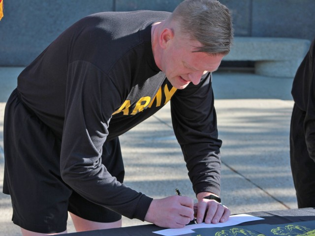 Maj. Gen. Darren Werner, Commanding General U.S. Army Tank-automotive and Armaments Command, signs an Army Emergency Relief donations form at the Detroit Arsenal, Michigan for the AER Run/Walk event May 14.