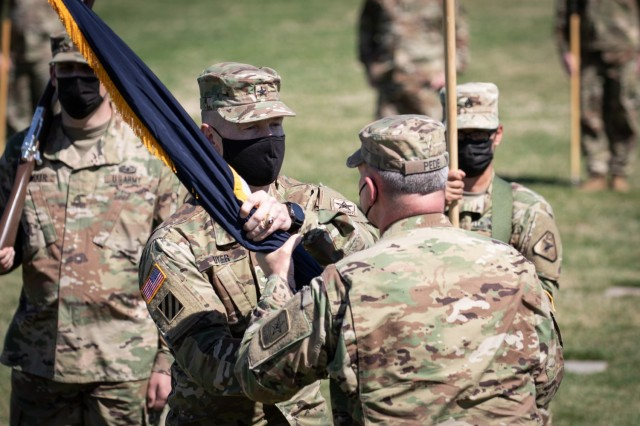 Brig. Gen. William Dyer III, center left, signifies his assumption of command by receiving the colors of the United States Army Reserve Legal Command from Lt. Gen Charles Pede, the Judge Advocate General of the United States Army, during a ceremony held Friday, March 26.