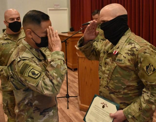 Command Sergeant Major Delfin Romani, Transatlantic Division CSM salutes Colonel John Haas Jr, after awarding him the Meritorious Service Medal at Camp Arifjan, Kuwait.