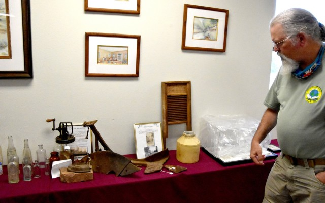 Scott Faris, Fort Polk field archaeologist, looks at some of the artifacts from the early 1900s found in the Joint Readiness Training Center and Fort Polk training area and now on display in the installation's Rock Shop.
