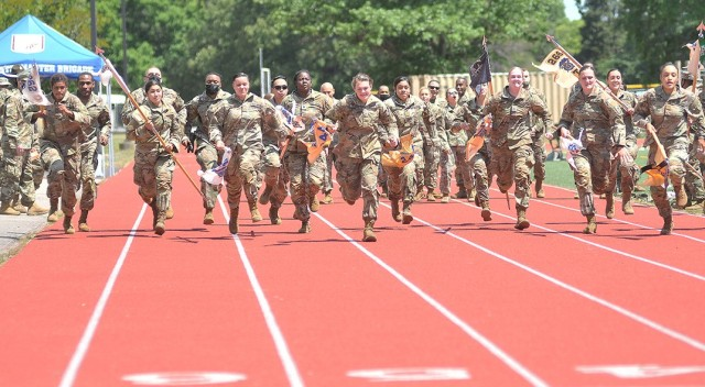 Dragon Brigade guidon-bearing Soldiers sprint toward the finish line during the Soldier Stakes Competition May 14 at Williams Stadium.