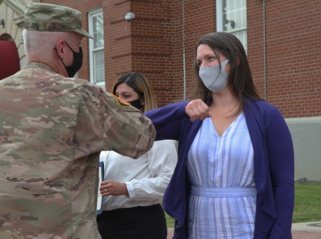 Mrs. Emily Shamsi, a member of the 1st Theater Sustainment Command Soldier and Family Readiness Support Group, gives a friendly elbow to Maj. Gen. John Sullivan, commanding general, 1st TSC, after receiving a Certificate of Appreciation at Fort Knox, Kentucky, May 14, 2021.  (U.S. Army photo by Pfc. Kaylee Harris 1st TSC Public Affairs)