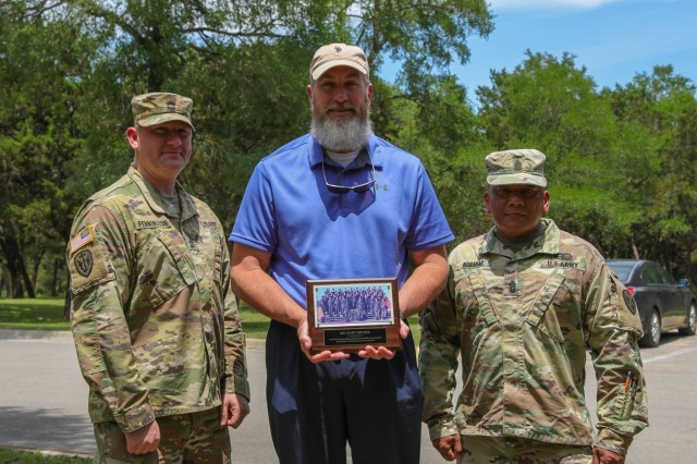 US Army Sgt. 1st Class Matthew Pennington, a counterintelligence agent (left), and Command Sgt. Maj. Michael R. Mabanag (right), both with the 504th Expeditionary Military Intelligence Brigade, presents Gary Wilder, Pennington's former drill sergeant (center), with a gift in Lions Park, Temple, Texas on May 7, 2021. The gift is a picture of Pennington's basic training class. (US Army photo by Pfc. Anthony X. Sanchez, 7th Mobile Public Affairs Detachment)