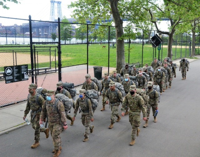 With the Williamsburg Bridge in the background, New York Army National Guard medics assigned to the Headquarters Company of the 1st Battalion, 69th Infantry Regiment hit the halfway point on a  six mile ruck march through Manhattan during the early morning hours on May 16, 2021. Thirty-six medics took part in the march as a train up for a required ruck march during annual training. U.S. Army National Guard photo by New York Guard Capt. Mark Getman.