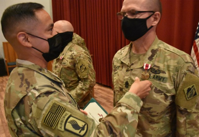 Command Sergeant Major Delfin Romani, Transatlantic Division CSM pins the Meritorious Service Medal on the lapels of Task Force Essayons outgoing Commander, Colonel John Haas, Jr. and outgoing Senior Enlisted Advisor, Sergeant Major William Klaers during the awards ceremony held within the Casing/Uncasing ceremony held at Camp Arifjan, Kuwait on May 15, 2021. (Photo by Rick Benoit)
