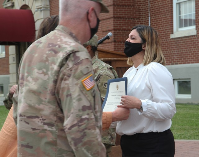 Mrs. Beatriz Medina, executive administrative specialist, 1st Theater Sustainment Command,  receives the Certificate of Appreciation from Maj. Gen. John Sullivan, commanding general, 1st TSC, at Fort Knox, Kentucky, May 14, 2021. (U.S. Army photo by Pfc. Kaylee Harris 1st TSC Public Affairs)
