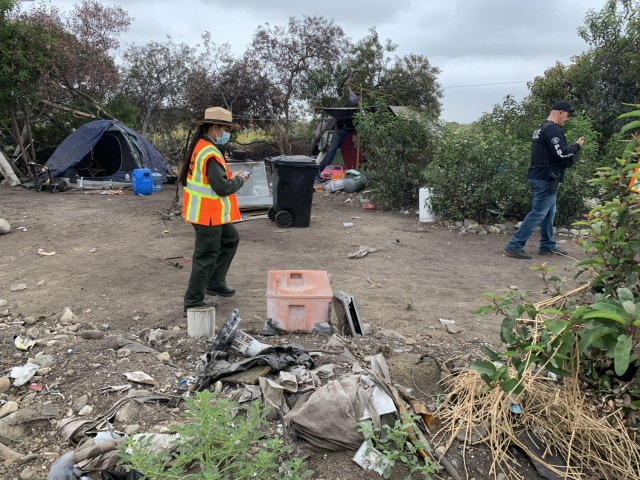 Park Ranger Annel Monsalvo, U.S. Army Corps of Engineers Los Angeles District, investigates one of dozens of abandoned campsites below the Santa Fe Dam, May 10, 2021, before crews arrive to clear out the debris.