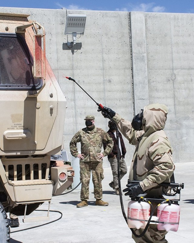 A Soldier from the 365th Chemical Company, 76th ORC sprays down a truck exterior to determine the presence of a simulated chemical agent during testing of the Contamination Indicator Decontamination Assurance System (CIDAS). The liquid turns a different color when encountering a simulated or actual chemical agent. Photo by Al Vogel, Dugway Public Affairs