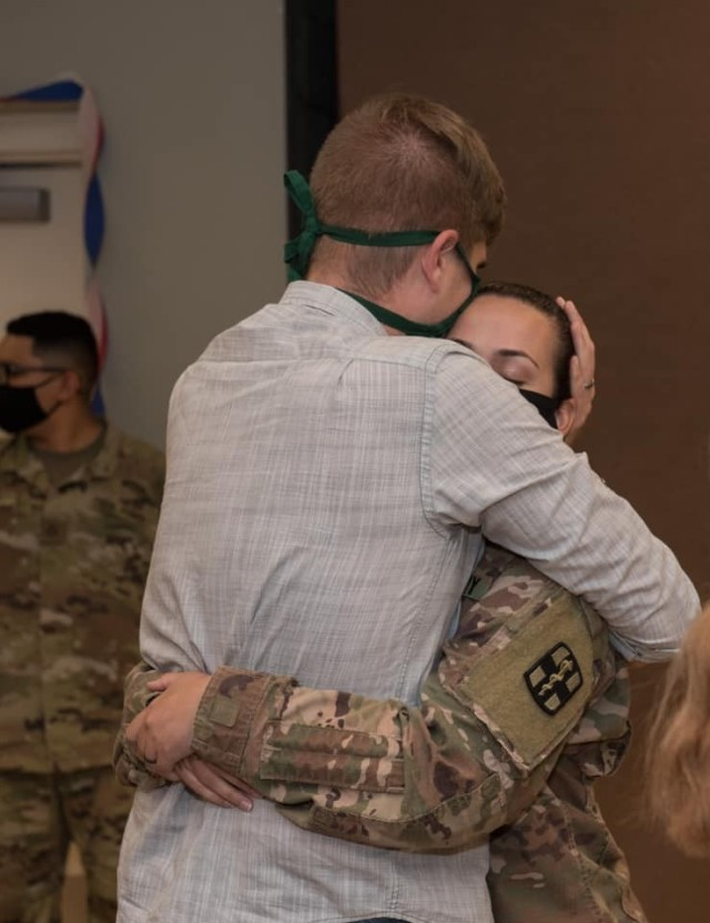 Capt. Kerstin Amezcua and her husband hug for the first time in months upon her return home from Kuwait.