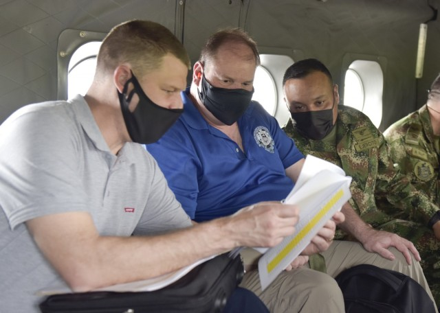 Joe Kidwell, left, the Colombian Central Case Manager at U.S. Army Security Assistance Command – New Cumberland, along with Jason King, center, the USASAC Colombian Country Program Manager, and their Colombian military counterpart, discuss foreign military sales cases during flight to see the Tolemaida Air Base, 6 April 2021. Kidwell, King and other members of the USASAC command leadership, visited several sites to see the impact of U.S. security assistance and foreign military sales, in support of the Colombian military in defending their country from counter-narcotic and terrorist threats. (U.S. Army photo by Richard Bumgardner)