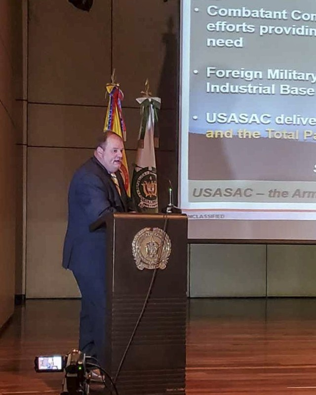 Jason King, the Country Program Manager, from Army Security Assistance Command, briefs the audience during a training class at the Colombian National Police headquarters, in Bogota, Colombia. King, and his counterpart from USASAC New Cumberland, Joseph Kidwell, conducted various training classes on the Foreign Military Sales process to 140 members of the Colombian Military, to include Colombian Army, Army Aviation, Air Force, Navy, Marines, National Police, Narcotics, and Ministry of Defense. Also in attendance was the Colombian vice Minister of Defense, Mr. Jairo García. (Courtesy photo)