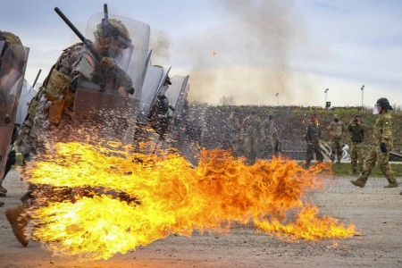 Iowa Army National Guardsmen run through a spray of gasoline and flames during fire phobia training at Camp Novo Selo, Kosovo, April 13, 2021.