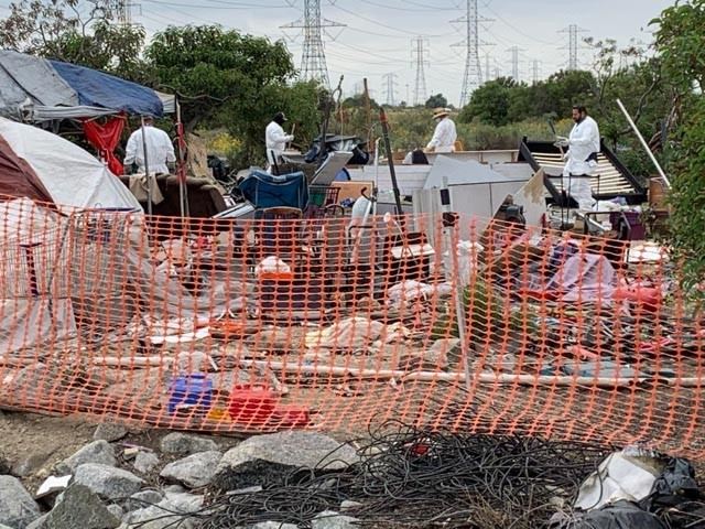 A cleanup crew from the U.S. Army Corps of Engineers Los Angeles District arrives at one of the abandonded campsites immediately below the Santa Fe Dam, May 10, 2021. The dam and Santa Fe Recreation Area adjacent to the 605 Freeway are maintained by the Corps for flood-risk management.