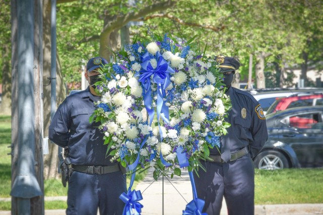 Officers from the Directorate of Emergency Services and New York Police Department pose behind the wreath used during Fort Hamilton's Law Enforcement Wreath Laying Ceremony, May 14, 2021, at Fort Hamilton, N.Y.