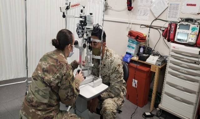 Cpt. Kerstin Amezcua conducts an eye exam on a Marine patient at Al Jaber Air Base.