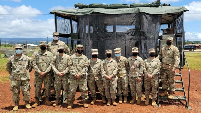 """Culinary Specialists assigned to Headquarters and Headquarters Company, 311th Signal Command (Theater) pause for a photo in front of their Mobile Kitchen Trailer with their NCO leaders, Staff Sgt. Jomar Matias, Sgt. Kem Nunn and Sgt. Alan Pilar, during range qualification operations at Schofield Barracks, Apr. 10, 2021. """"I am proud of our Culinary Specialists,"""" Matias said, """"and how much motivation we brought to the range."""""""